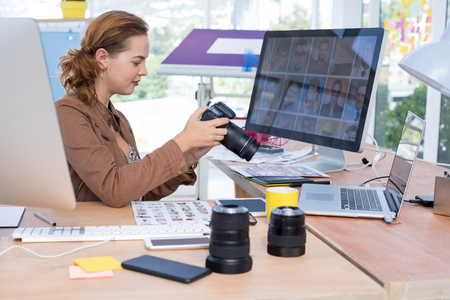 stylus: Female executive reviewing captured photograph at her desk in office Stock Photo