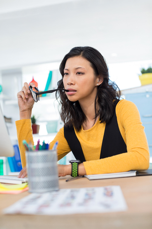 Thoughtful female executive working at desk in office Stock Photo