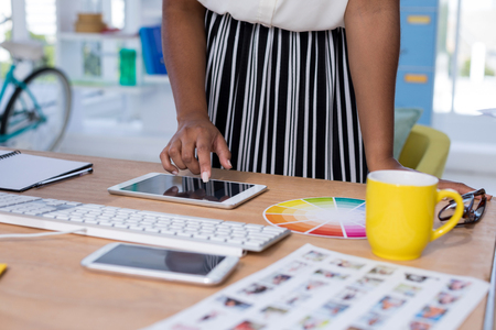 stylus: Mid-section of female designer using digital tablet in office Stock Photo