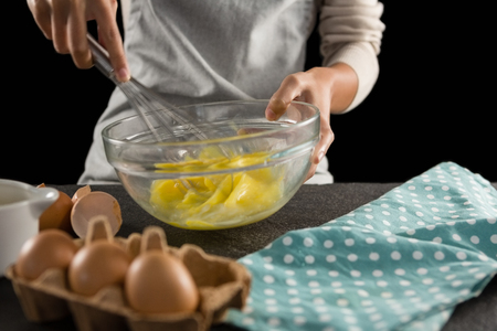 Mid section of woman beating eggs with a whisk in a bowl