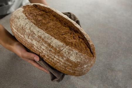Close-up of woman holding a loaf of bread Stock Photo