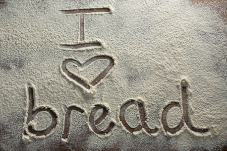 Close-up of the word I love bread written on sprinkled flour