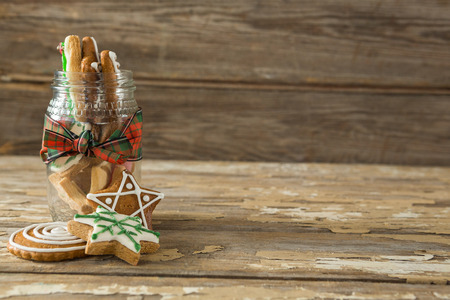 Gingerbread cookies in jar on wooden plank Stock Photo