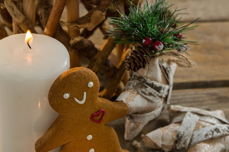 Gingerbread cookie by illuminated candle and star shape decorating on table