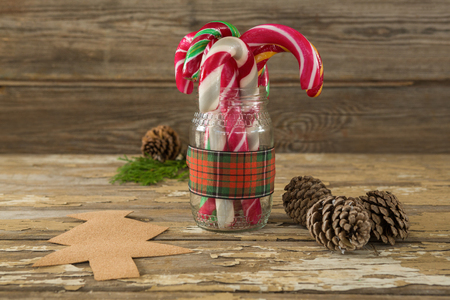 Pine cones and candy cane in jar against wooden plank during christmas time