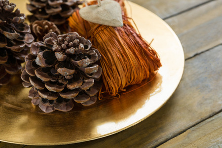 High angle view of pine cones with thread in plate on table