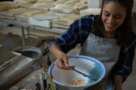 Female potter painting a bowl in pottery workshop