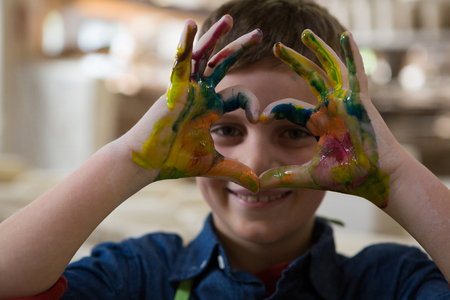 Boy gesturing with painted hands at pottery workshop Banco de Imagens