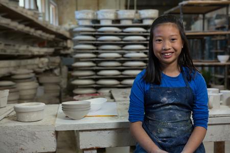 Portrait of happy girl standing near worktop in pottery workshop