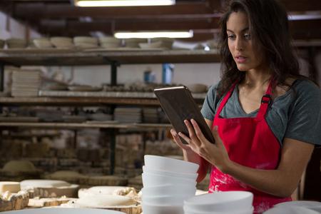Female potter using digital tablet in pottery workshop