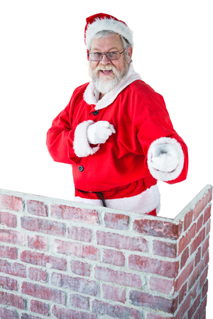 Portrait of santa claus standing behind the chimney and pointing against white background