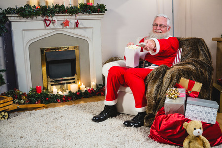 Kerstman zit en houdt afstandsbediening van de televisie