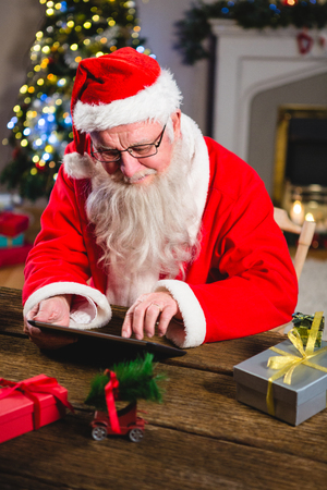 Santa Claus using digital tablet on table at home