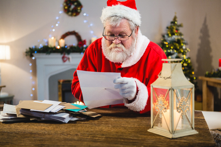 Santa Claus reading a letter at home 版權商用圖片 - 87883671