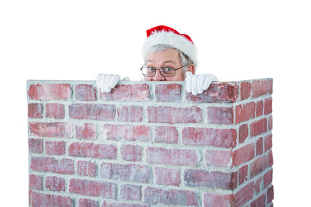 Santa claus hiding behind a chimney against white background