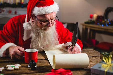 Babbo Natale avere caffè durante la scrittura su scorrimento a casa