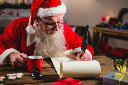 Santa Claus having coffee while writing on scroll at home Stok Fotoğraf