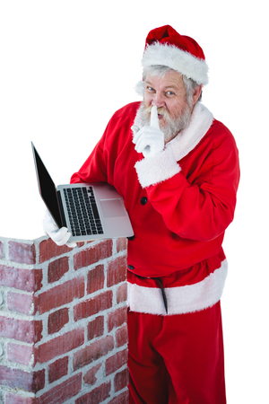 Portrait of santa claus with finger on lips while using laptop against white background Stock Photo