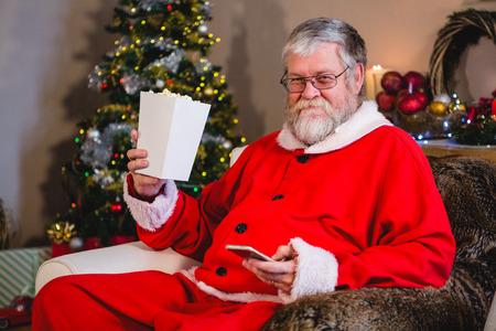 Santa Claus using mobile while having popcorn at home