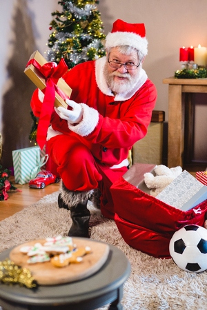 Santa Claus putting presents in christmas bag at home