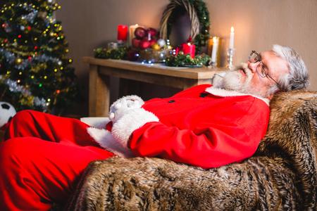 Santa claus taking a nap on sofa at home