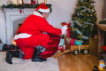 Santa Claus arranging gifts near christmas tree at home Stock Photo