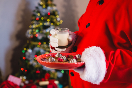 Santa Claus holding plate of sweet food with glass of milk at home