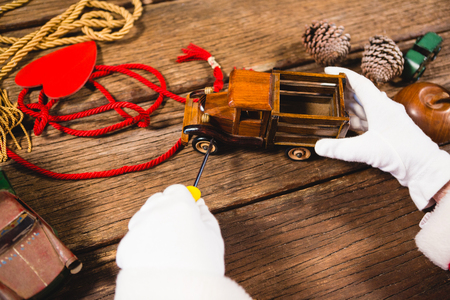 Close-up of santa repairing toy car during christmas time