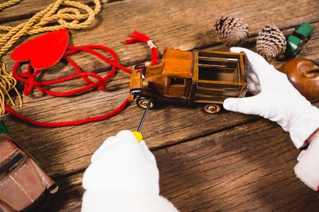 Close-up van santa die stuk speelgoed auto herstelt tijdens Kerstmistijd Stockfoto