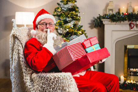 Santa claus with gift boxs sitting on chair with finger on lips in living room during christmas time Stock Photo