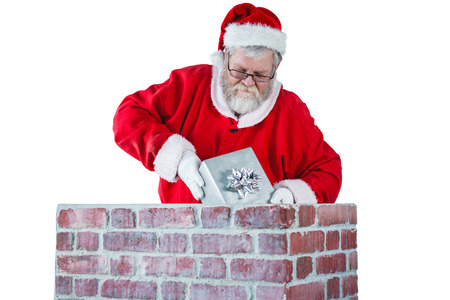 Santa claus placing gift box into a chimney during christmas time