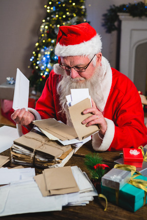 Santa Claus removing a letter at home