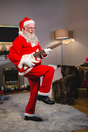 Smiling santa claus playing a guitar during christmas time at home