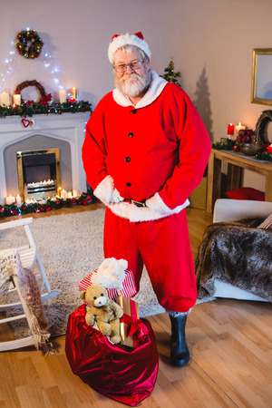 De Kerstman die zich met zijn handen op taille thuis bevinden