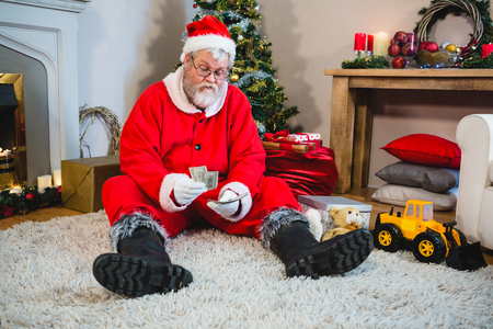 Santa claus sitting on the floor and counting cash at home