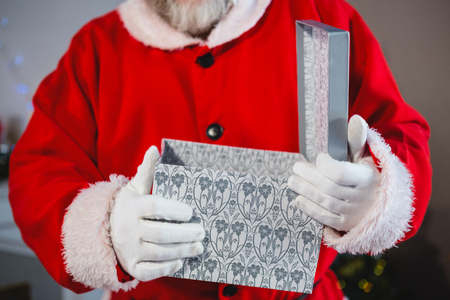Mid-section of santa claus opening the gift box