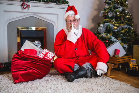 Santa claus with gift sack sitting on rug with finger on lips in living room at home Stock Photo