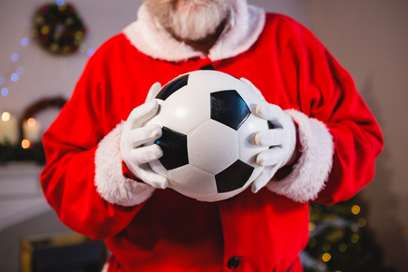 Mid-section of santa claus holding a football