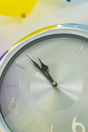 Close-up of balloon and clock hands reaching 12 o clock midnight Stock Photo