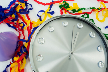 Close-up of clock and streamers against white background Stock Photo