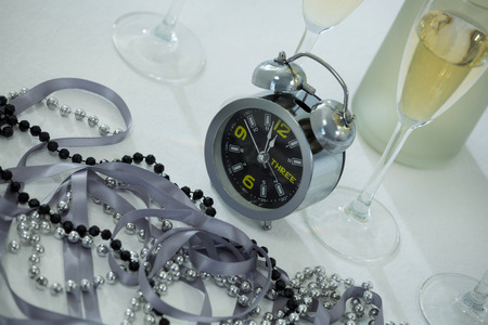Close-up of champagne with alarm clock and glass on white background Stock Photo