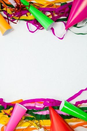 Overhead of colorful streamers and party hat on white background