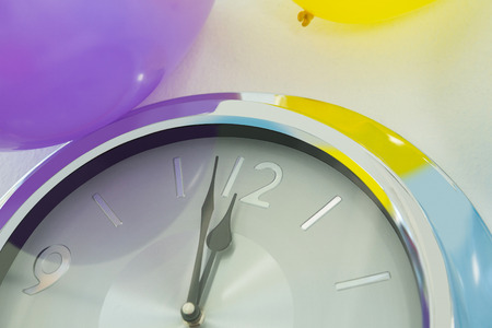 Close-up of balloons and clock hands reaching 12 o clock midnight