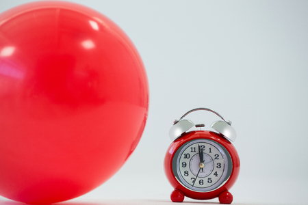 Close-up of red balloon and alarm clock on white background