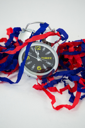 Close-up of alarm clock and streamers against white background Stock Photo