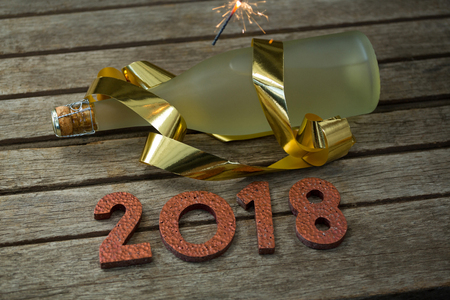 Ignited sparkler, bottle of champagne and year 2018 on a wooden surface Stock Photo