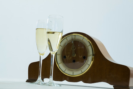 Close-up of champagne glass and clock on white background