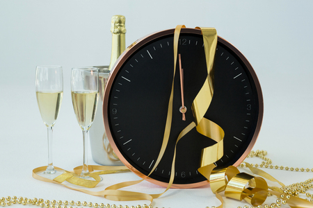 Close-up of champagne with clock and glass on white background Stock Photo
