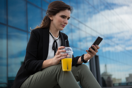 Female executive using mobile phone in office premises