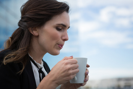 premises: Young female executive having coffee in office premises